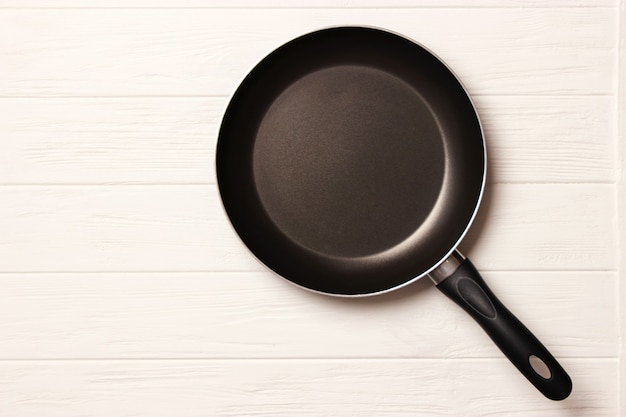 Frying pan and on the wooden table top view cooking