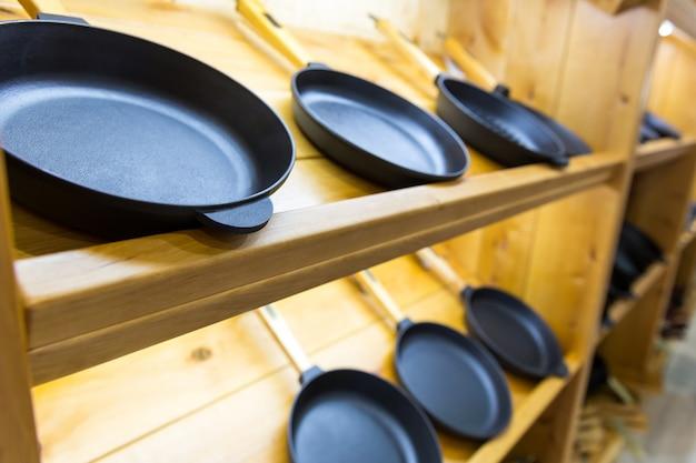 Сковороды на деревянной полке, инструменты для приготовления пищи