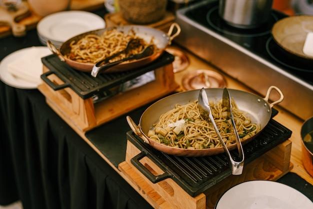 Сковороды со спагетти на чугунной плите на кухне с белыми чистыми тарелками