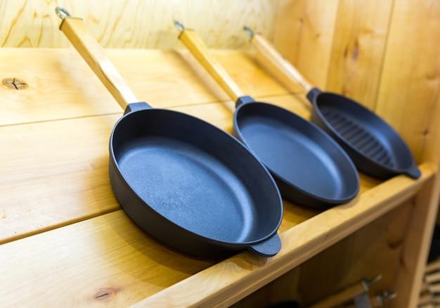 Frying pans on wooden shelf closeup