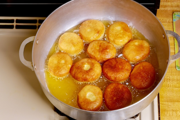 Frying round tasty donuts in hot oil in deep pan.