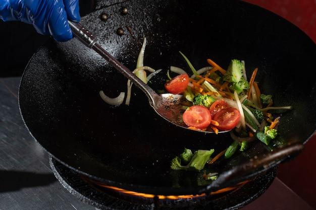 냄비에 야채 튀김 양파, 브로콜리, 토마토 체리, 당근, 아스파라거스.