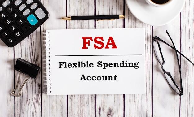 Счет гибких расходов fsa записан в белом блокноте рядом с калькулятором, кофе, очками и ручкой.