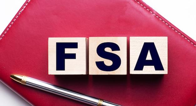 Счет гибких расходов fsa, состоящий из деревянных кубиков, которые стоят на бордовом блокноте рядом с ручкой.