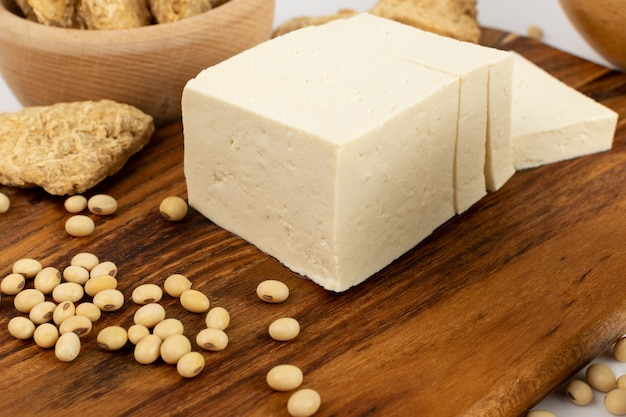 Сыр фтеш тофу или веганский сыр на деревенском виде сбоку стола. нарезанный соевый творог, соевый белок или tsp