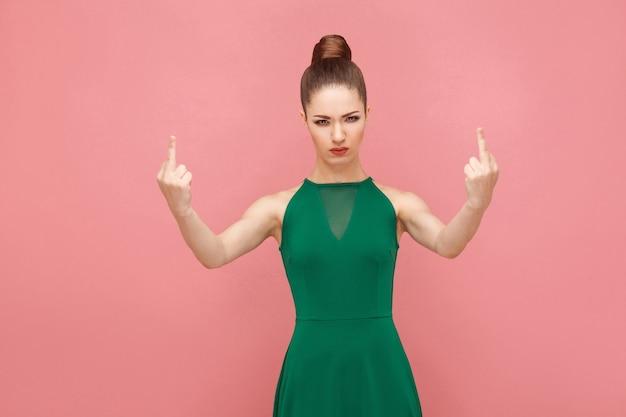 すべてファック!カメラで悪い兆候を示している女性。表現感情と感情の概念。ピンクの背景に分離されたスタジオショット