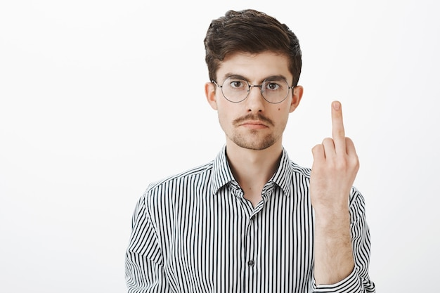 Fuck off, man, i am not your slave. annoyed serious adult male with bristle and moustache, showing middle finger and staring with calm expression, being fed up of mocking over gray wall