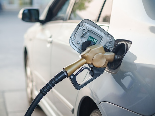 Fuel nozzle refueling a car at gas station