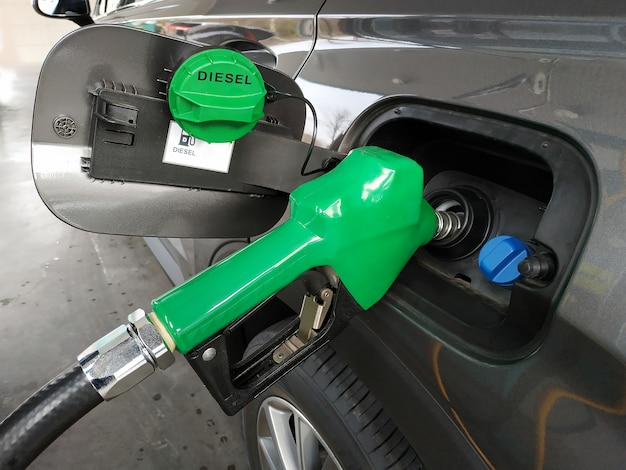 Fuel nozzles adding diesel fuel in car at a pump gas station.