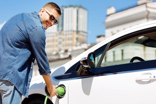 燃料の補充。彼の車を補充しながら燃料ノズルを保持しているうれしそうなハンサムな男
