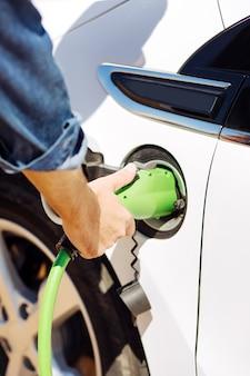 燃料ステーション。給油中に車に取り付けられている燃料ノズルのクローズアップ
