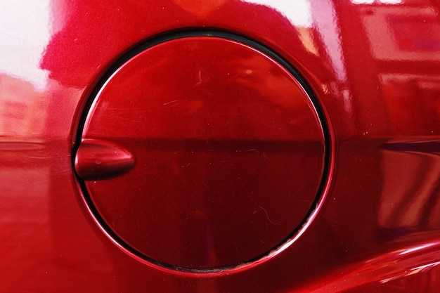 Fuel tank cap of a red passenger car. side view.