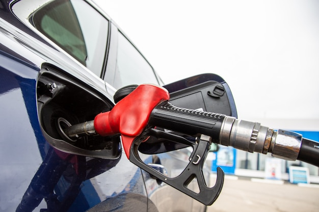 Fuelling gun inserted into the tank of blue car