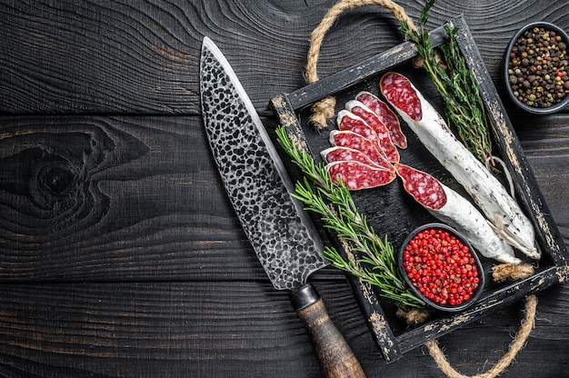 Fuet salami sausage slices with thyme and rosemary in a wooden tray. black wooden background. top view. copy space.