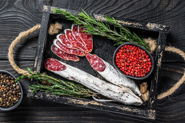 Fuet salami sausage slices with thyme and rosemary in a wooden tray. black wooden background. top view.