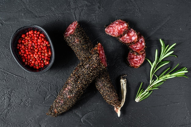 Fuet, salami and a sprig of rosemary. traditional spanish sausage. black background. top view
