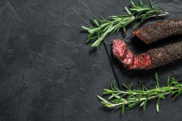 Fuet, salami and a sprig of rosemary. traditional spanish sausage.