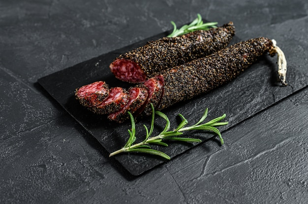 Fuet, salami and a sprig of rosemary.