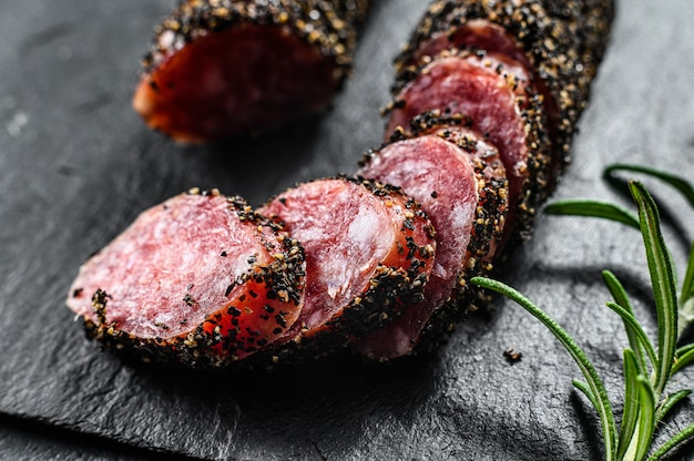 Fuet sausage cut in slices on a black slate plate with rosemary. black background. top view