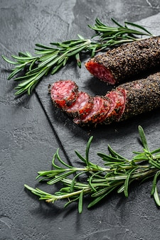 Fuet sausage cut in slices on a black slate plate with rosemary. black wall. top view