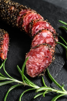 Fuet sausage cut in slices on a black slate plate with rosemary.
