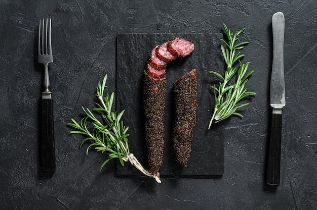 Fuet sausage cut in slices on a black slate plate with rosemary