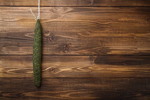 Колбаса fuet на светлой деревянной поверхности, вид сверху с копией пространства.