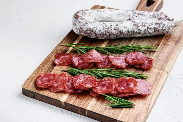 Fuet целые и нарезанные отрубы, испанская сухая вяленая колбаса на белом текстурированном фоне.