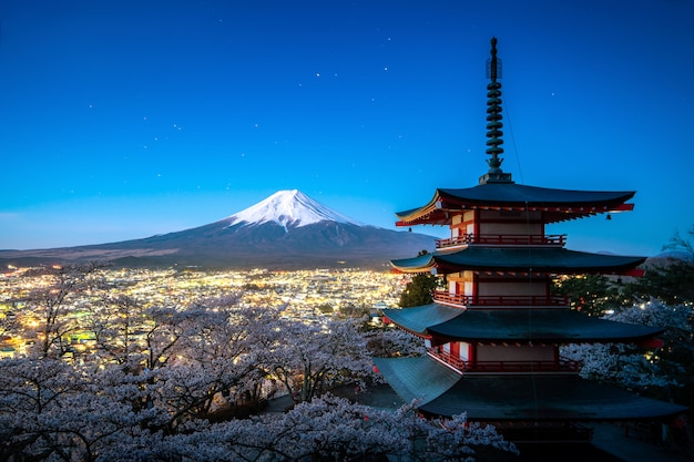 Fujiyoshida, japan at chureito pagoda and mt. fuji in the spring with cherry blossoms full bloom during twilight. japan