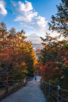 Благоустраивайте изображение горы фудзи с красными лист в осени на заходе солнца на fujiyoshida, японии.