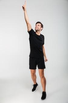 Ritratto di ful llength di un giovane sportivo sorridente in piedi