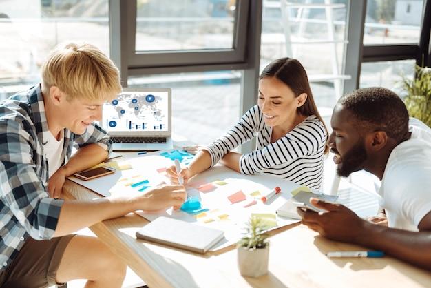 アイデアのフル。テーブルに座ってメモを取り、戦略を立てる新しい戦略に取り組んでいる陽気な若者のグループ