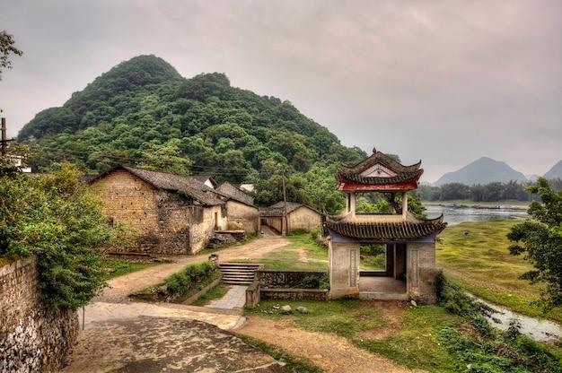 富麗精品家、陽朔、広西、中国山村の入り口にある石塔パーゴラ観光名所中国農村部の桂林景勝地、春、昼間。