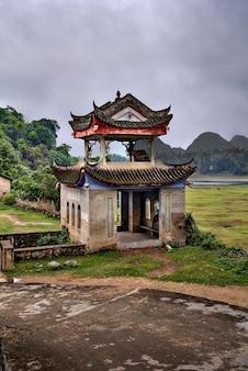 カルスト丘陵と放牧草地に囲まれた、古代の村の春の端にある、中国農村部の美しい農業地帯にあるフーリ村、陽朔、広西、ストーンパーゴラパゴダ。