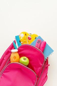 Полный рюкзак со школьными принадлежностями и обедом на белом фоне. накладные расходы, копирование пространства