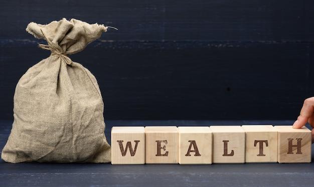 Полный мешок и богатство надписи на деревянных кубиках. концепция сбережений и накоплений. долгосрочные инвестиции, синяя поверхность