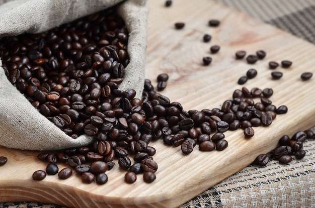 A full bag of brown coffee beans lies on a wooden surface