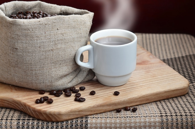 A full bag of brown coffee beans and a white cup of hot coffee l