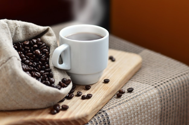 A full bag of brown coffee beans and a white cup of hot coffee