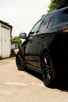 Полный черный японский автомобиль на улице гаража в солнечный день