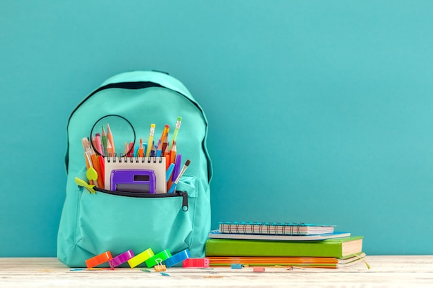 Full blue school backpack with different supplies on blue background.