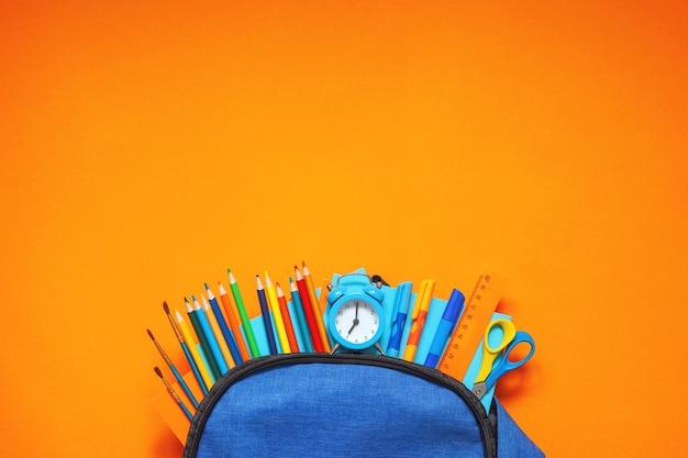 Полный синий школьный рюкзак с различными принадлежностями на оранжевом фоне.