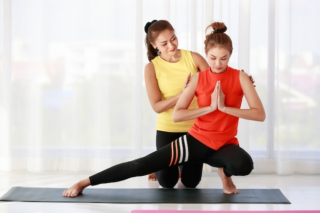 スタジオでのヨガレッスン中にサイドランジポーズをしている新人女子学生の肩に触れる全身アジア人トレーナー