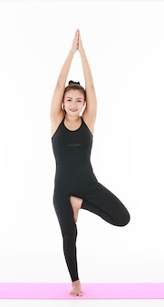 Full body asian woman doing vriksasana pose and looking at camera while practicing yoga against white background