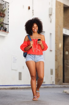 Full body beautiful black woman walking with mobile phone and earphones