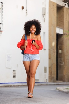Full body beautiful cheerful woman walking with mobile phone and earphones