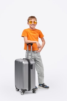 Full body cheerful kid traveler smiling and leaning on suitcase while standing on white background before journey