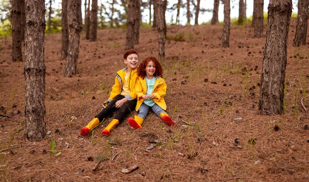 Full body of cheerful little redhead sister and brother wearing similar yellow raincoats and rubber boots, sitting on dry grass in autumn forest with coniferous trees