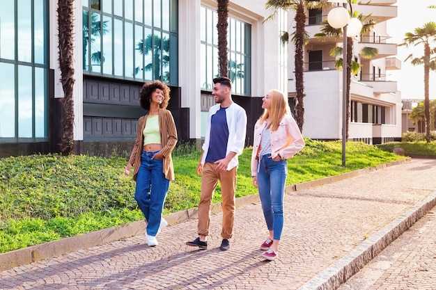 Full body of cheerful young multiracial students in trendy casual outfits chatting and laughing friendly while strolling together on pavement near modern buildings in summer day in city