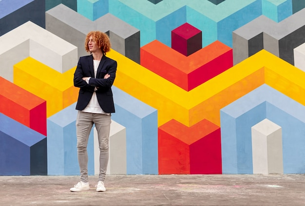 Full body of cheerful young stylish male with re curly hair in trendy outfit standing on street with crossed arms and looking away, against colorful geometric graffiti wall